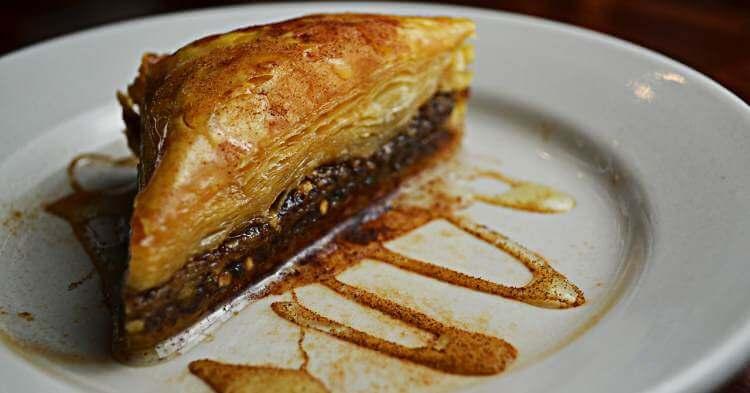 Parče baklave prelivene šećernim sirupom na belom tanjiru