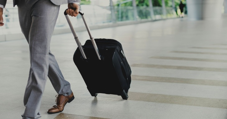 Čovek u poslovnom odelu vuče svoj kofer