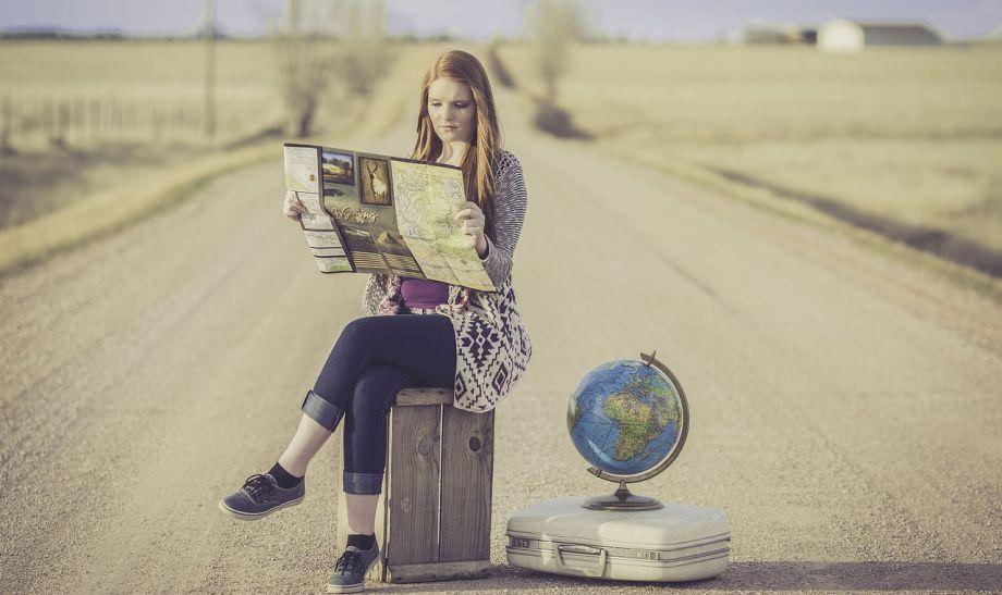 Devojka sedi na koferu