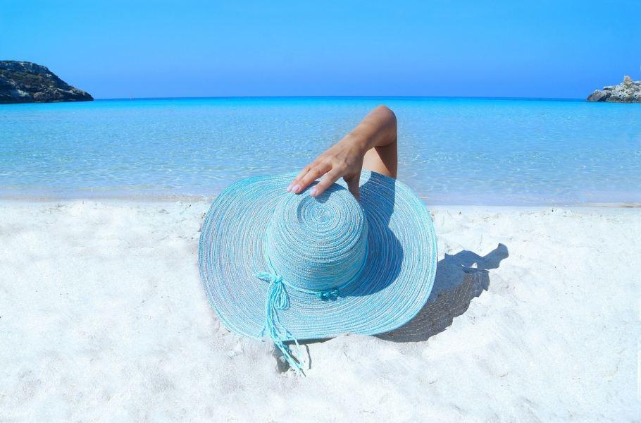 Devojka sa plavim šeširom na plaži