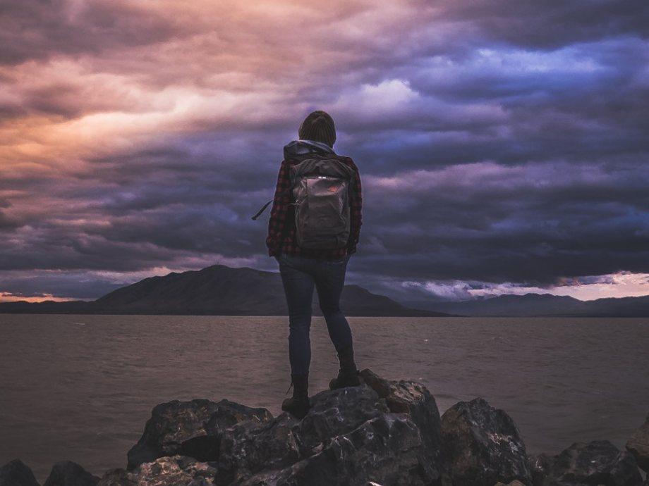 Devojka stoji na steni pored mora