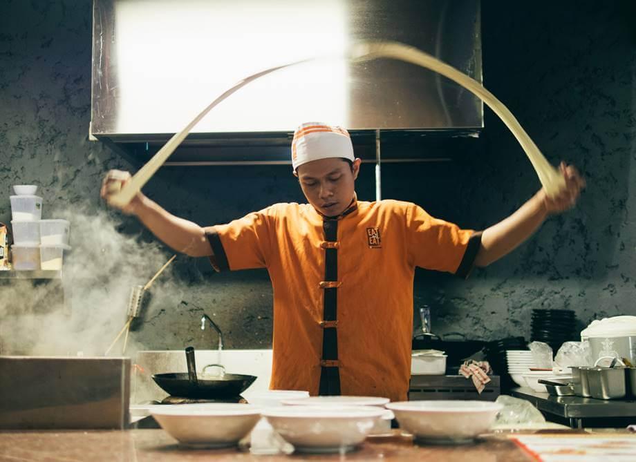 Kineski kuvar sprema hranu u kineskom restoranu
