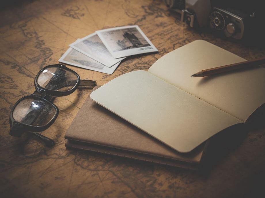 Sveska, mapa i naočare na stolu