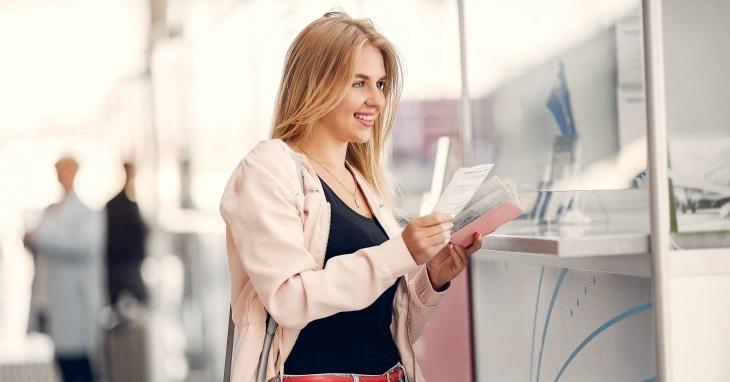 Devojka stoji ispred šaltera i drži dokumenta