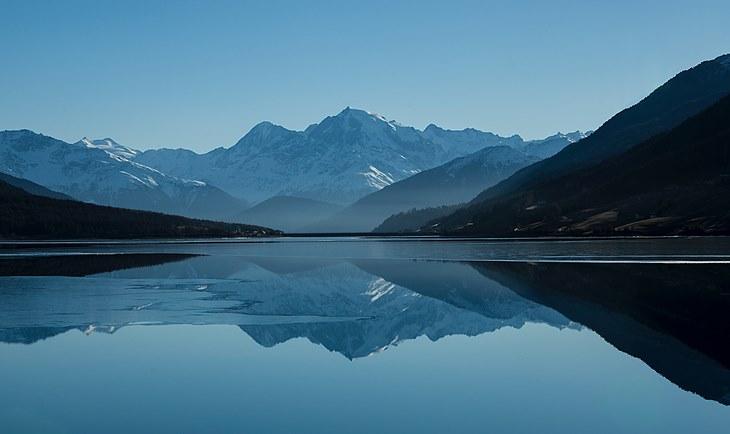 Fotografija maglovitog jezera iza koga se nalazi planina