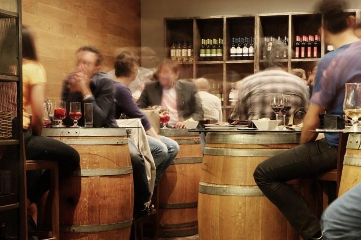 Bar u kome sede ljudi za barskim stolovima u obliku bureta