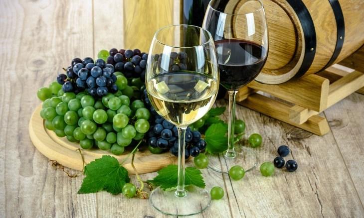 Dve čaše crnog i belog vina poreg kojih se nalazi crno i belo grožđe