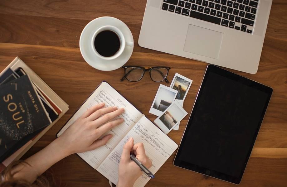 Psianje dnevnika na stolu pored koga se nalazi kafa,laptop i naočare