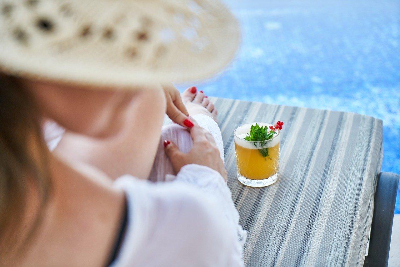 Devojka pije koktel na plaži