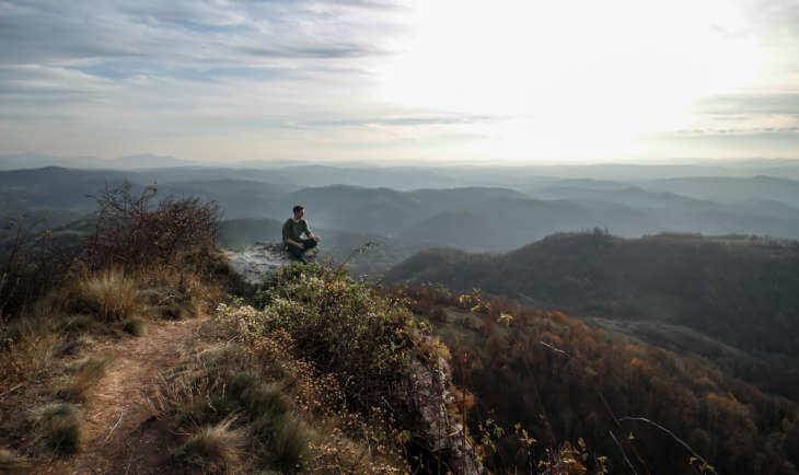 Čovek na vrhu planine sa koje se proteže prelep vidik