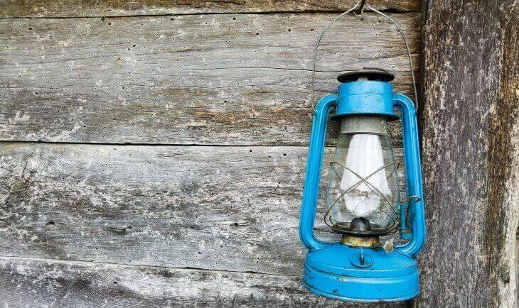 Plava petrolejka okačena na drvenoj kući