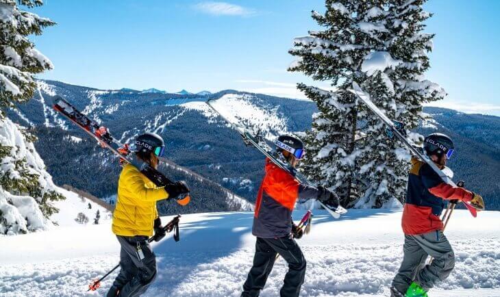 Tri skijaša na planini idu kroz sneg sa skijama u rukama