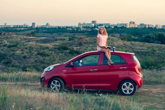 Deovjka sedi na krovu crvenog automobila