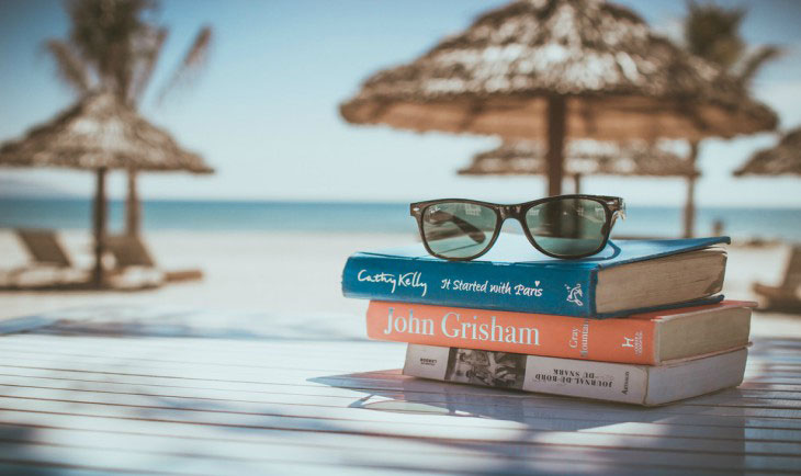 Tri knjige na stolu na plaži jedna na drugoj i na vrhu naočare