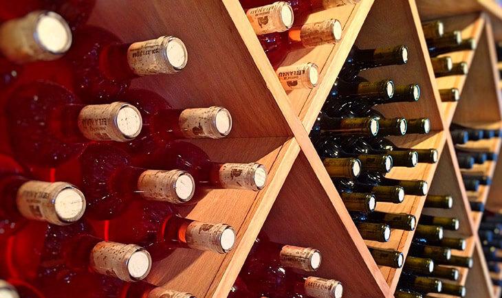 Boce vina poredjane na drvenim policama u vinskom podrumu