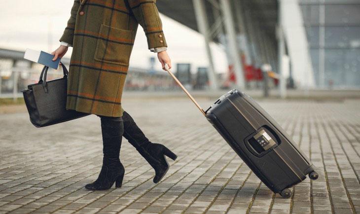 Žena u kaputu spremna za put, nosi pasoš, manju torbu i kofer