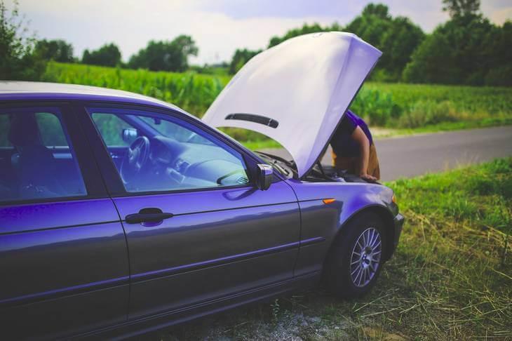 Prikaz zaustavljenog automobila i čoveka koji ga popravlja