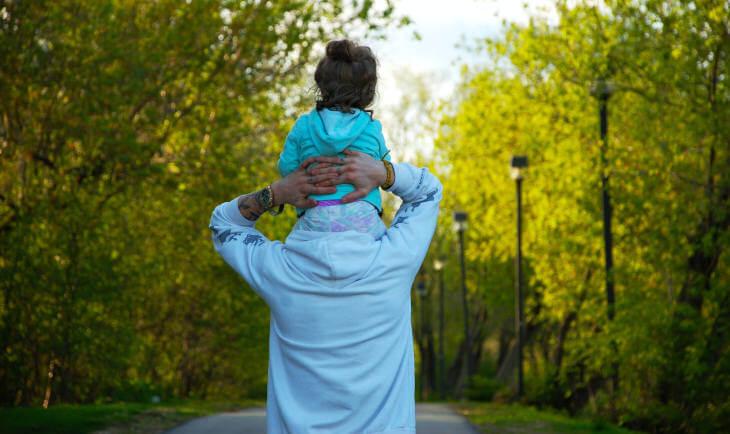 Čovek koji nosi devojčicu na ramenima