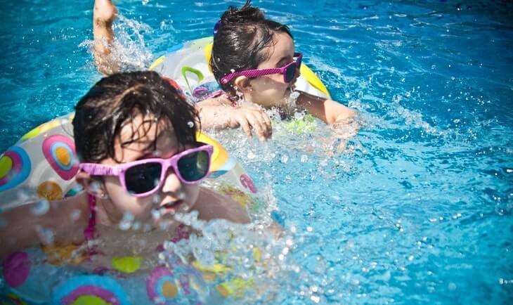 Dečak i devojčica plivaju sa zaštitnim šlaufima u akva parku na Srebrnom jezeru