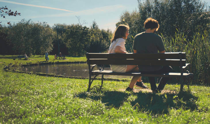 Prikaz muškarca i žene koji sede na drvenoj klupi u prirodi