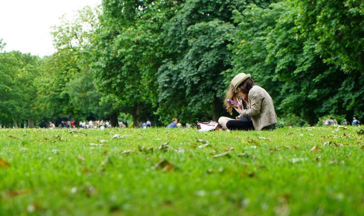 Prikaz dvoje ljudi koji sede na travi u prirodi