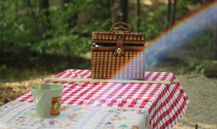 Prikaz piknik korpe i crvenog stolnjaka u prirodi
