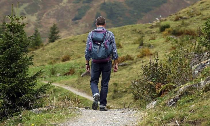 Čovek u planinarskoj odeći šeta u prirodi