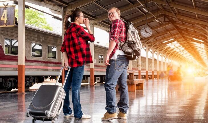 Ljudi na autobuskoj stanici sa putnim torbama