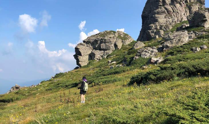 covek stoji na travi planinskom vrhu a iza njega su stene