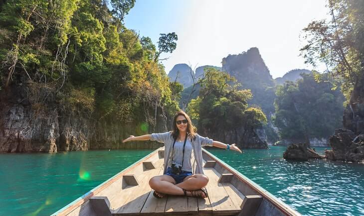 nasmejana devojka na čamcu krstari egzotičnom destinacijom
