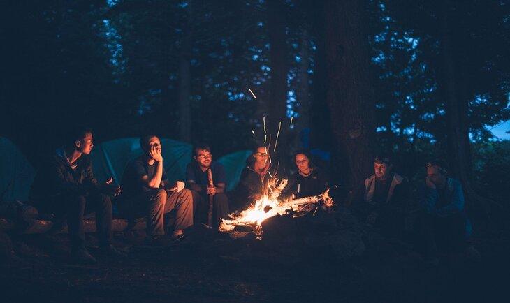 prijatelji okupljeni na travi oko vatre