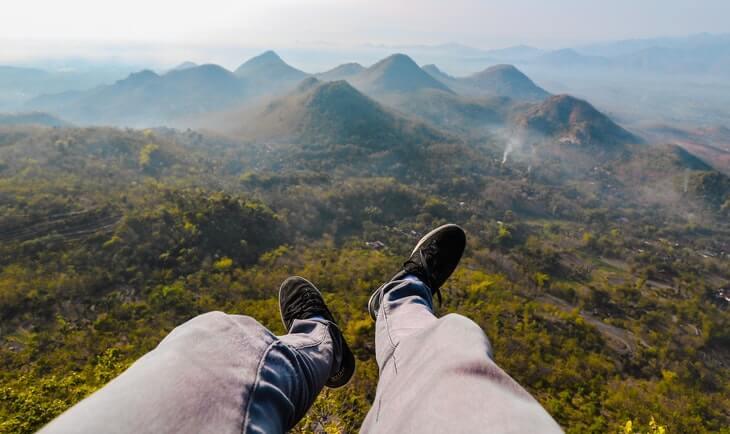 pogled sa planine i čovek koji sedi na vrhu