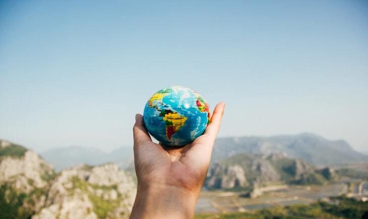 prikaz ruke u kojoj je mali globus
