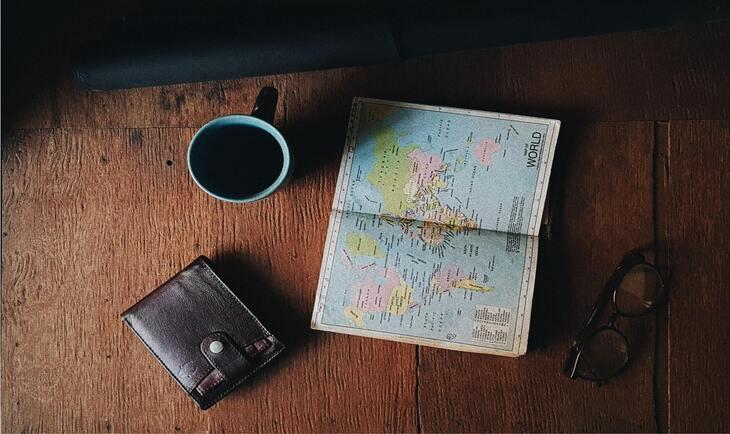 novčanik, karta sveta i šolja sa kafom